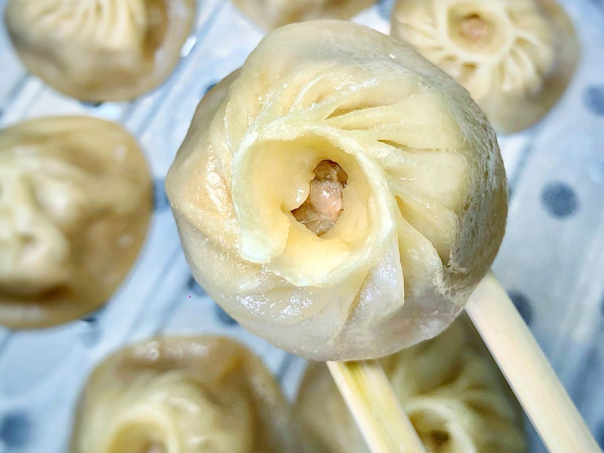 Dumplings with one on a pair of chopsticks