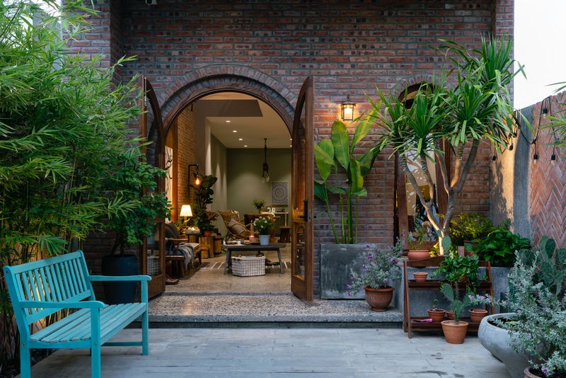 The entrance to the home features a brick arched doorway with wooden door. A blue bench sits on the left with potted plants on the right. You can see into the home's living room.