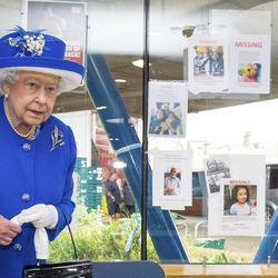 Britain's Queen Elizabeth II, stands near to a wall with photos of missing people,  during a visit to the Westway Sports Centre which is providing temporary shelter for those who have been made homeless by the fire at Grenfell Tower,  in London,  Friday June 16, 2017. Relatives of those missing after a high-rise tower blaze in London are searching frantically for their loved ones, as the police commander in charge of the investigation says he hopes the death toll will not rise to three figures.
