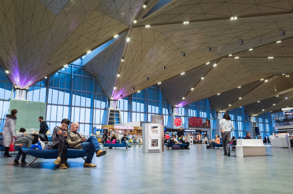 The interior of Pulkovo Airport in Russia. There is an angled geometric ceiling. There are floor to ceiling windows.