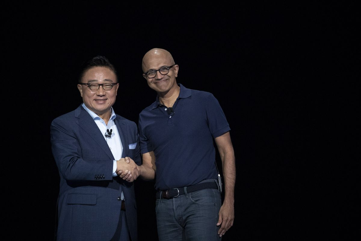 Microsoft CEO Satya Nadella shakes hands with then Samsung Electronics CEO DJ Koh.