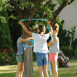 A group of young girls tie ribbons on a tree as community members gather to tie ribbons and write messages to the Rackley family and first responders of the murder-suicide along Alta Canyon Drive in Sandy on Saturday, June 10, 2017.