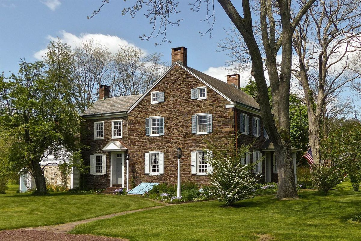Exterior shot of three-story stone Colonial house with gabled roof, multiple chimneys, and window shutters.