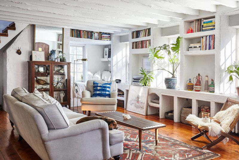 A living room with a grey sofa, coffee table, white bookshelves with books, and multiple windows letting in natural light. There is a patterned area rug on the floor and a white armchair.