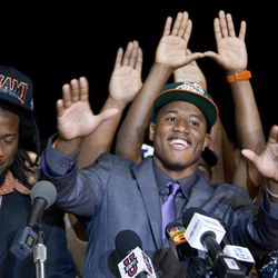 Tracy Howard, the Miramar, Fla. high school football player, announces Tuesday, Feb. 1, 2012 that he will attend the University of Miami, as his best friend, Malcolm Lewis, left, and his mother, Shaiy, react to the announcement. Lewis, a team mate is, also, attending UM.