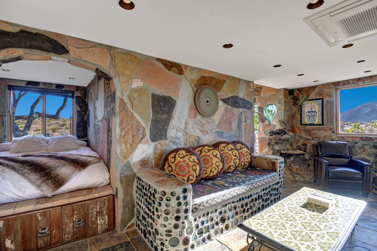 A stone living room with a large couch, coffee table, and a bed in a sleeping alcove to the left.