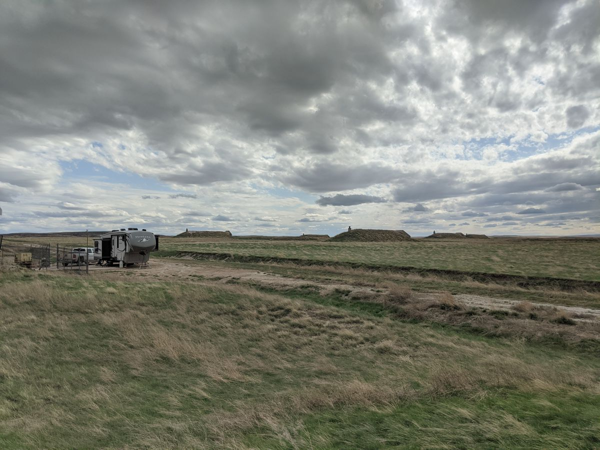 A landscape photo showing Tom and Mary's truck, camper van and neighboring bunkers with a cloudy sky.