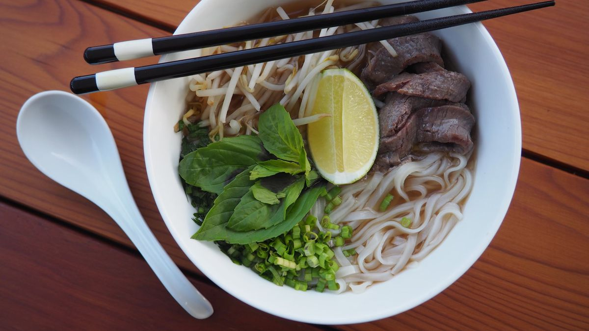 bowl of pho (rice noodle dish with herbs, lime wedge, and beef) on wood table