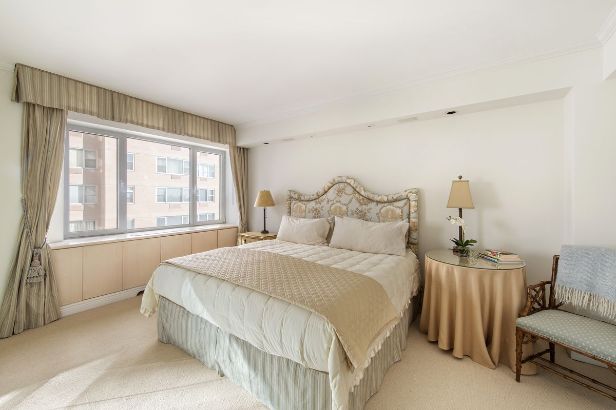 A bedroom with a large bed and a large window with curtains.