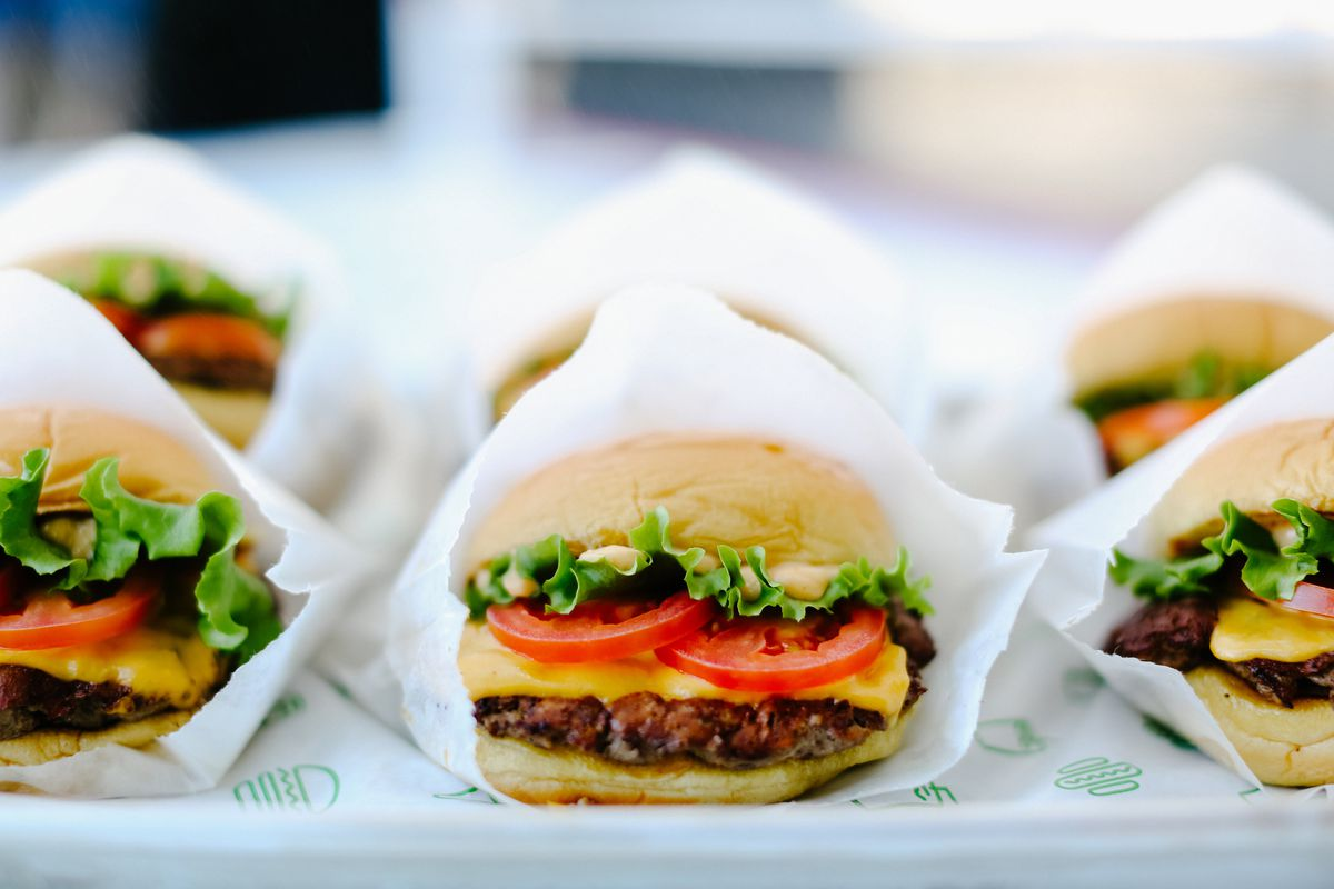 Burgers with tomato, lettuce, and cheese wrapped in white paper sitting side by side on a tray