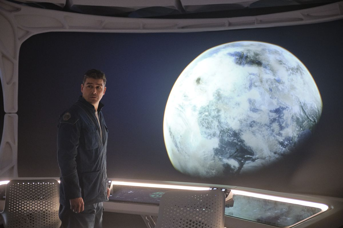 Kyle Chandler looks out a window at a planet in The Midnight Sky