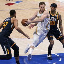 Utah Jazz center Rudy Gobert (27) and guard Jordan Clarkson (00) defend as Dallas Mavericks forward Nicolo Melli, center, drives to the basket for a shot in the second half of an NBA basketball game in Dallas, Monday, April 5, 2021.