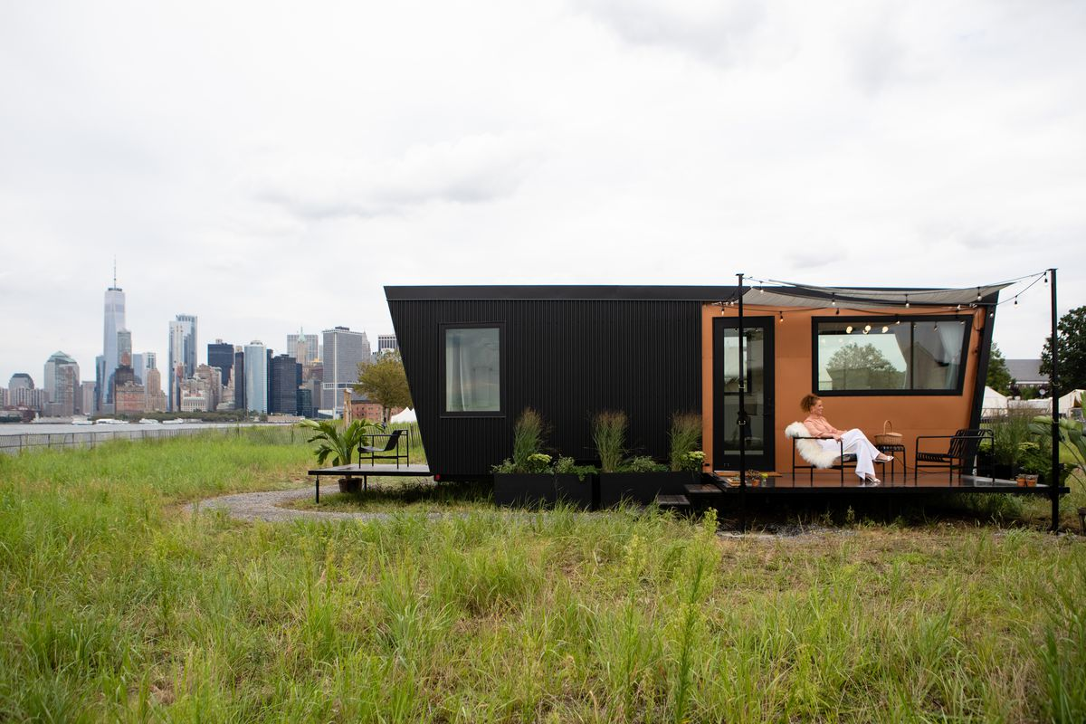 A tiny home with a black and wood exterior, with a small door and two windows. There is a porch connected to the house, with a man sitting in a chair on it. The house is parked on an island, with tall buildings in the background.