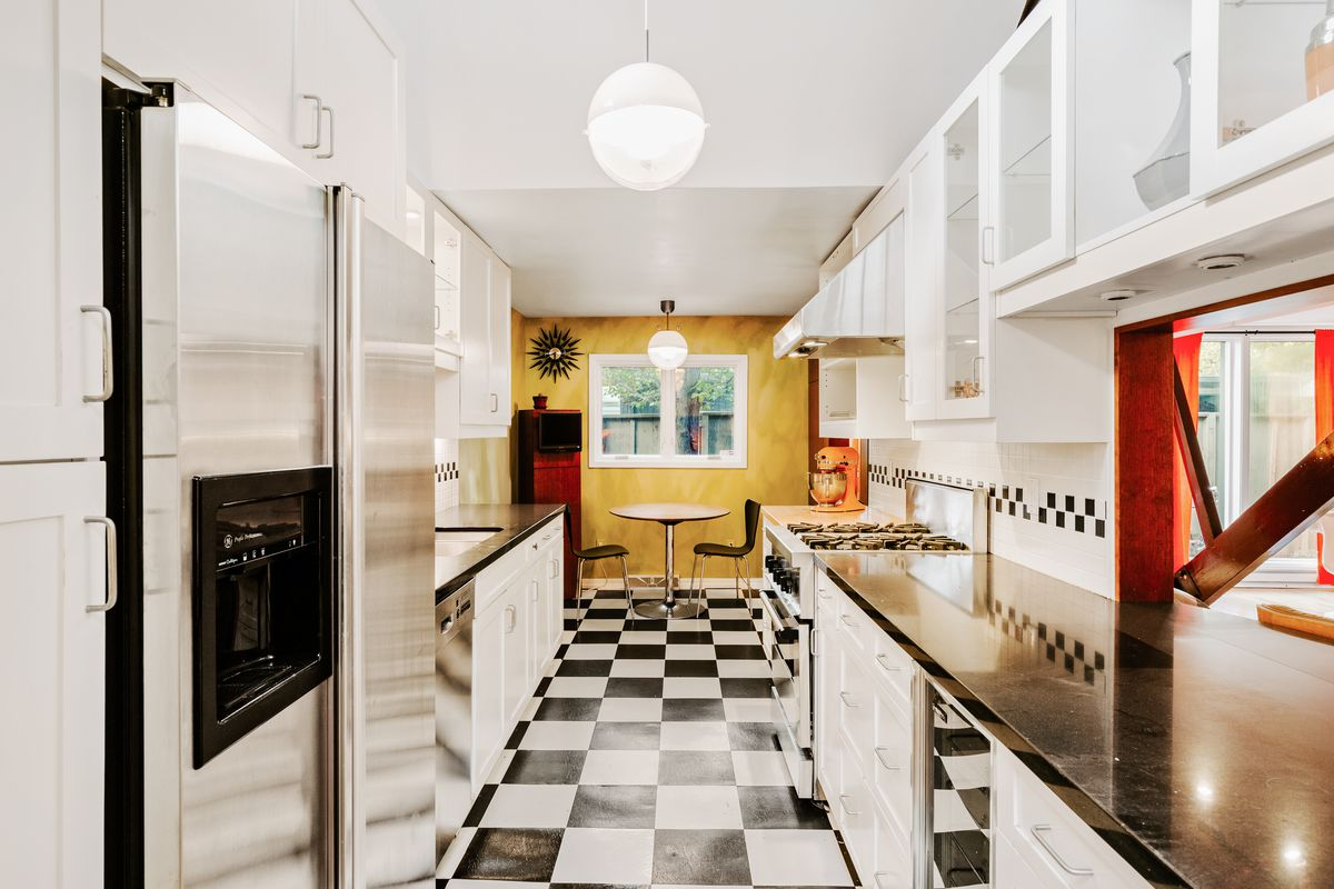 A long and narrow kitchen has black and white tiles, black counter tops, and white cabinets.