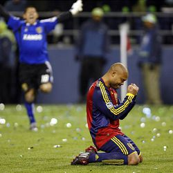 Real Salt Lake's Robbie Russell kneels and begins celebrating after making the winning goal while goalkeeper Nick Rimando runs to congratulate.