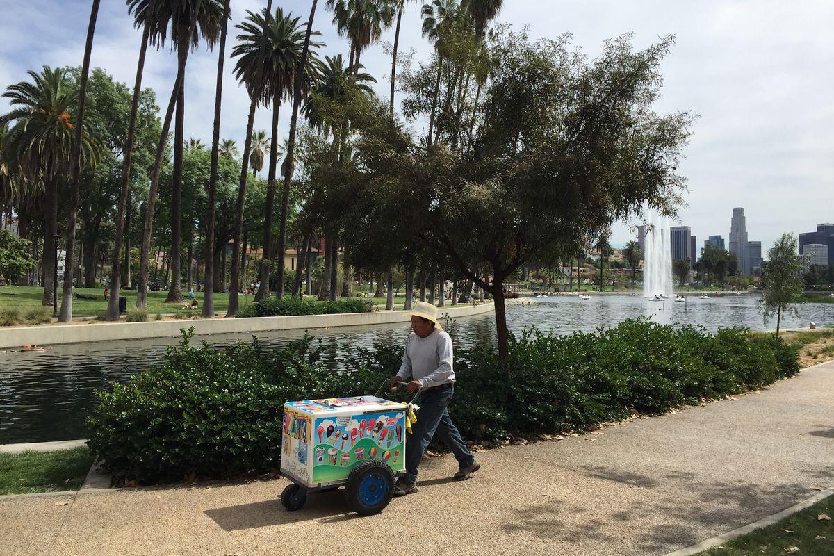 A street food vendor in the summer pushes a cart along a sandy path near a park lake.