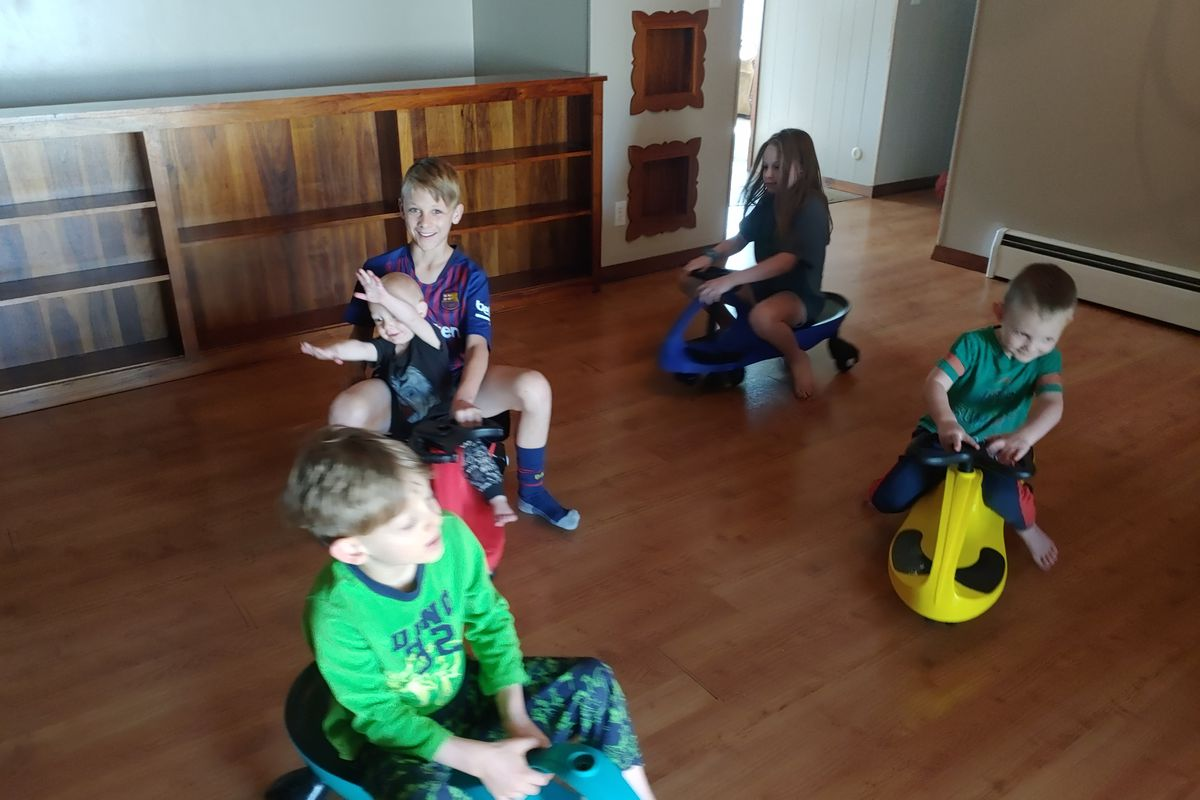 Five of Arianne Brown's eight kids ride around on wiggle cars in the family's dining room.