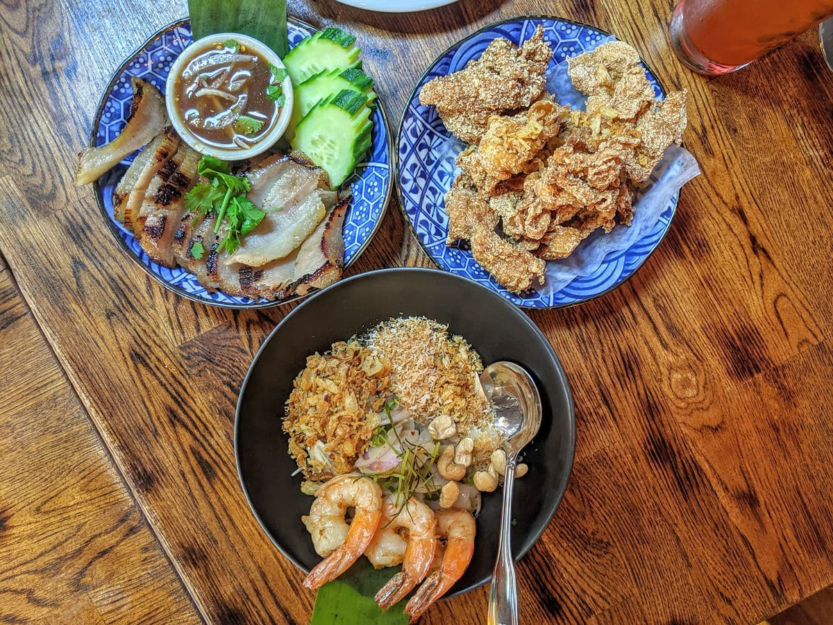 Overhead view of three dishes of food on a wooden table. One blue dish has thin slices of pork jowl, cucumber, and a dipping sauce; another blue dish has hunks of crispy chicken skin; and a black dish has a salad featuring shrimp and pieces of rambutan.