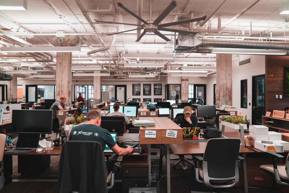 Workers inside a coworking space, filled with rows of shared desks and an exposed industrial ceiling.