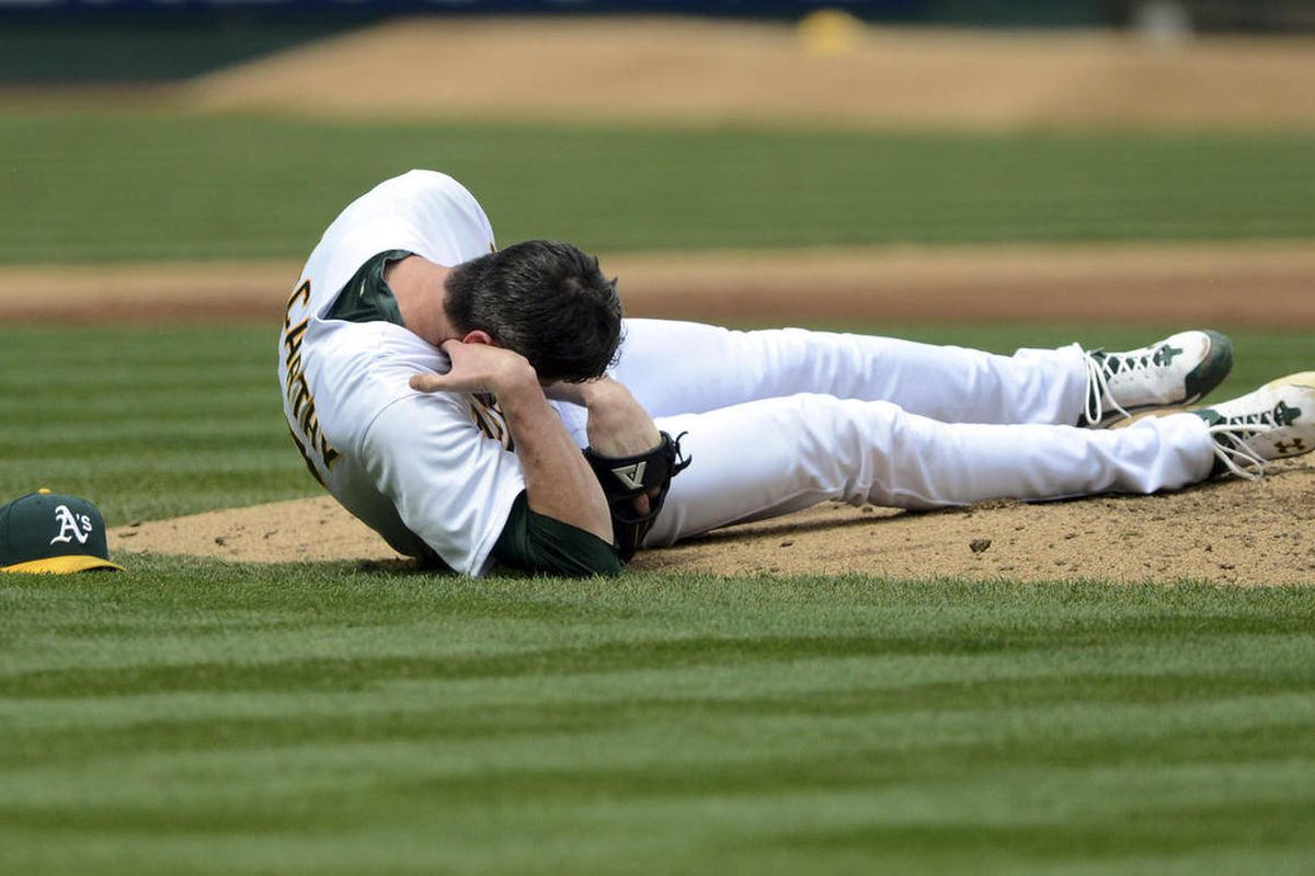 Oakland Athletics pitcher Brandon McCarthy (32) holds his head after being struck by a ball hit by Los Angeles Angels' Erick Aybar in the fourth inning of a baseball game, Wednesday, Sept. 5, 2012, in Oakland, Calif. McCarthy was sent to the hospital, and