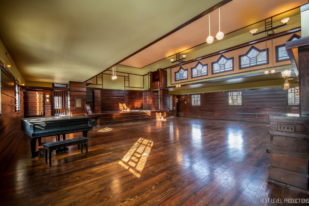 A two-story room with wood floors and panels on the walls. The upper portions are painted earth tones and lined with geometric windows.
