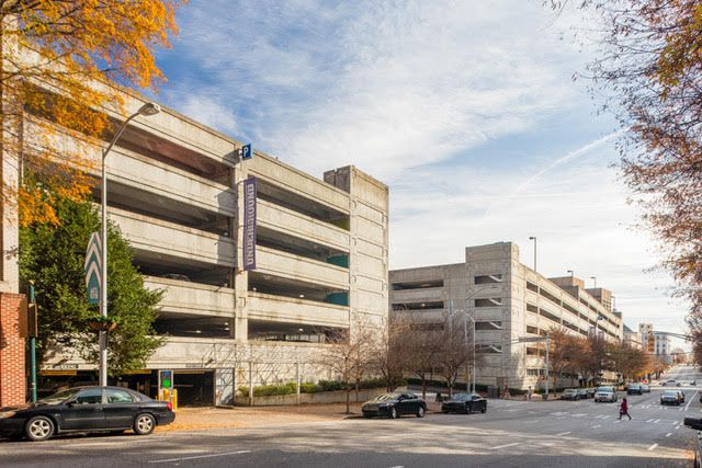 Two parking garages with autumn leaves at left and people crossing the street in front.
