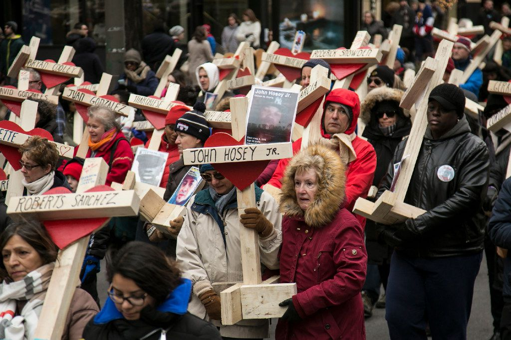A cross bearing the name and photo of John Hosey Jr., one of the 16 people killed in Beat 1133 last year, was carried down Michigan Avenue in a march organized by the Rev. Michael Pfleger at the end of 2016. | Ashlee Rezin / Sun-Times