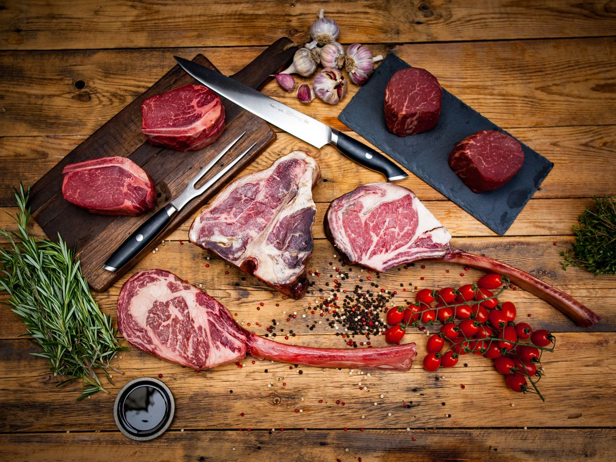 Steaks on a wooden table.