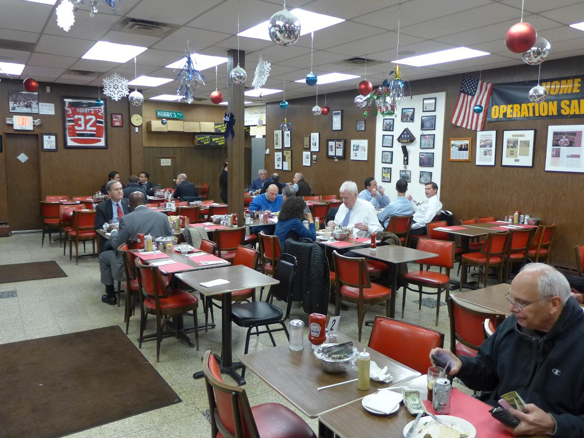 Customers sit together in pairs and small groups in a diner featuring with leftover holiday decorations and American flags