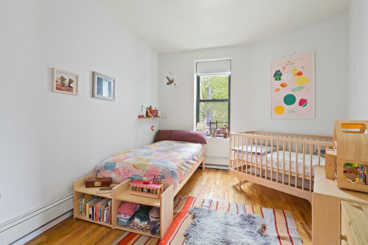 A small bedroom with a window, a crib, a small bed, hardwood floors, and a shelf with books and clothes.