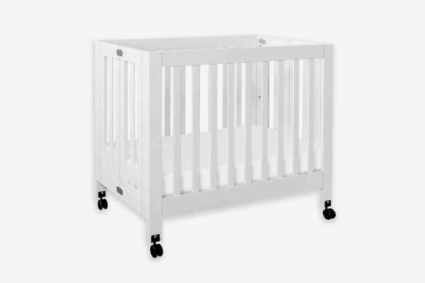 White crib with black wheels.