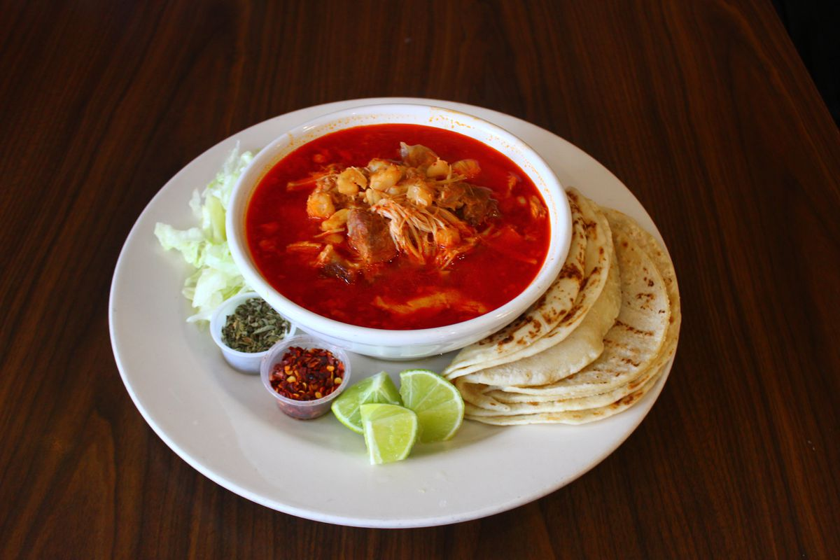 The pozole with tortillas on the side, along with garnishes and limes.