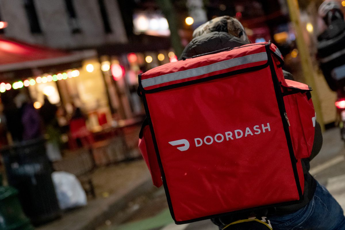 """A food delivery worker with an orange backpack that reads """"DOORDASH"""" bikes through a New York City street"""