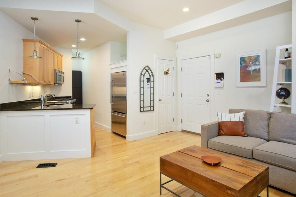 An open living room-kitchen area just beyond a front door in a condo.