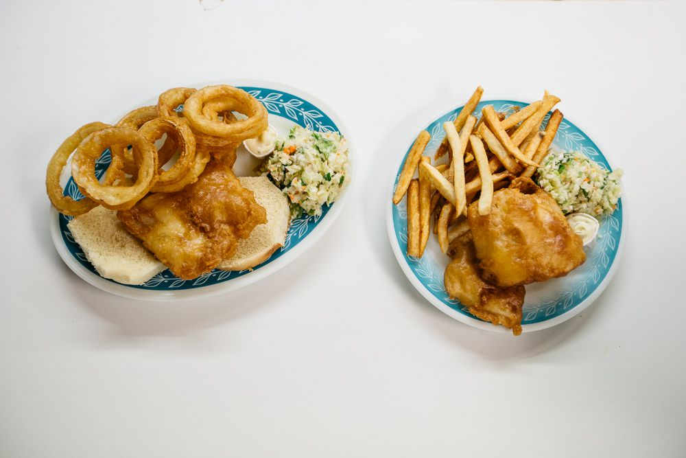 Two blue and white patterned plates filled with fish and chips, coleslaw, rolls, fries, and onion rings.