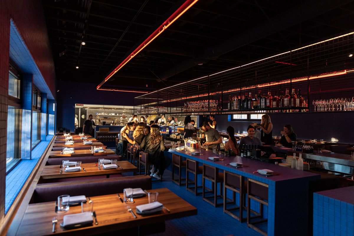 The interior of Magnet is shown as sun streams through the windows and on to customers seated at a rectangular bar with blue tile and floating metal racks over head.