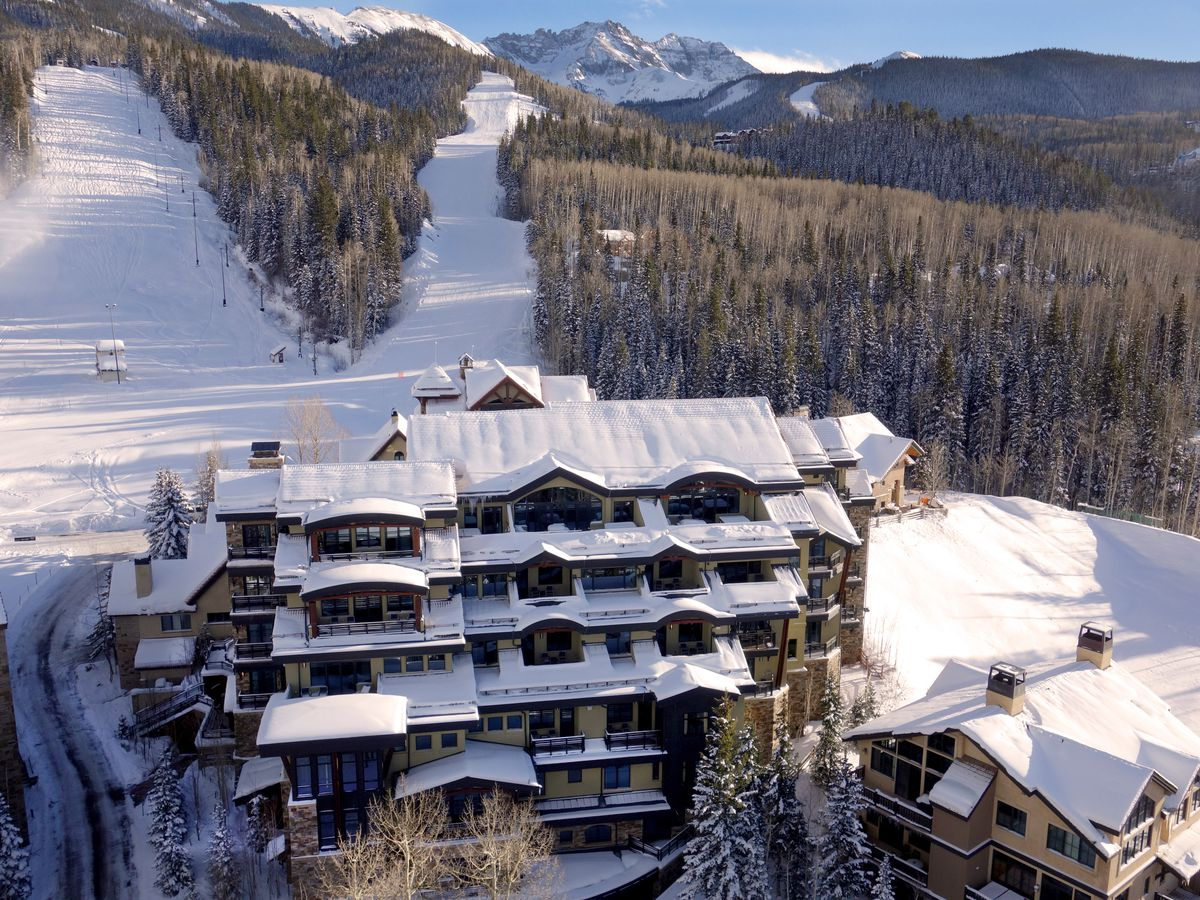 An aerial view of a multi-story condo building with snowy roofs that sits in front of ski runs and trees.