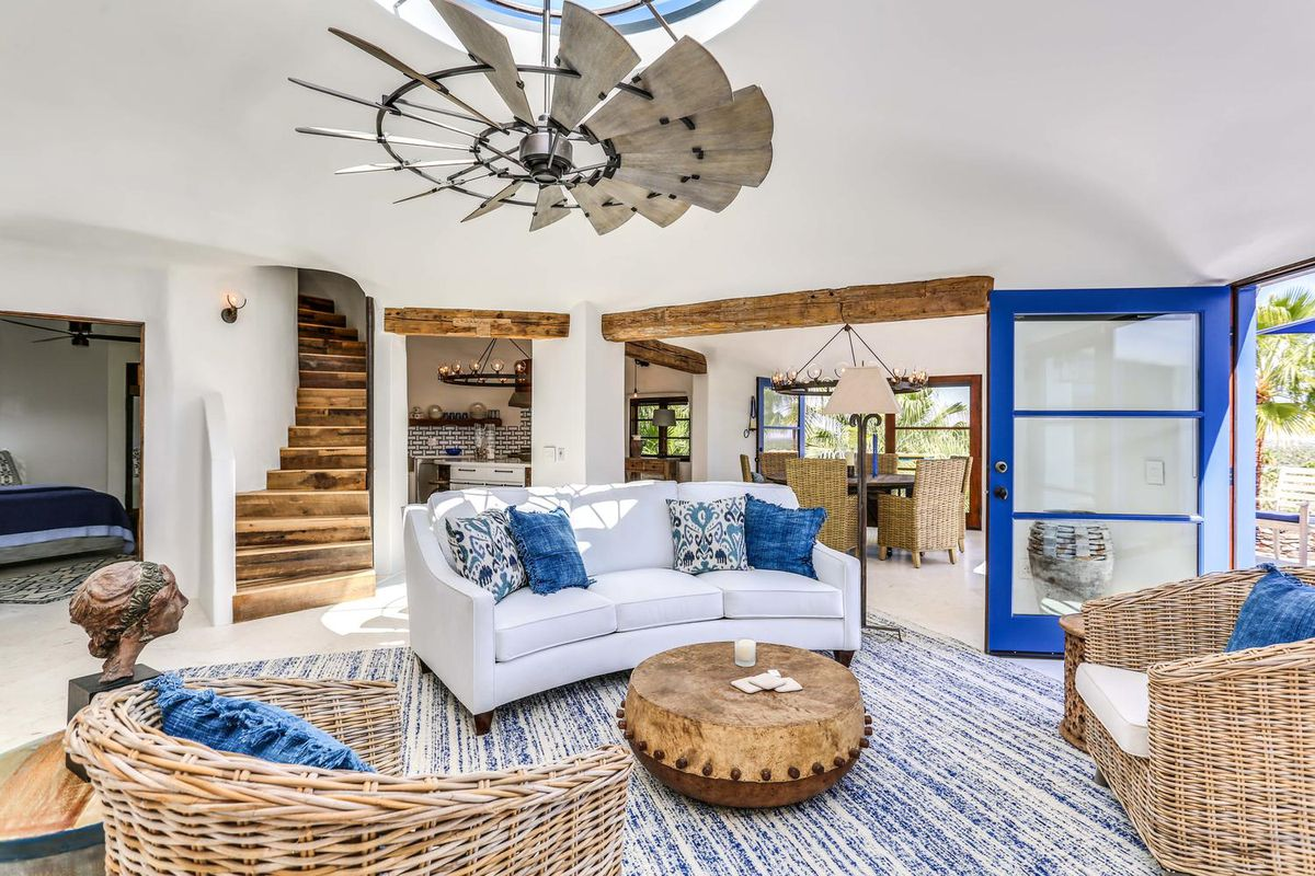 A living room has a blue and white rug, white couch, rattan arm chairs, and blue doors out to a patio.