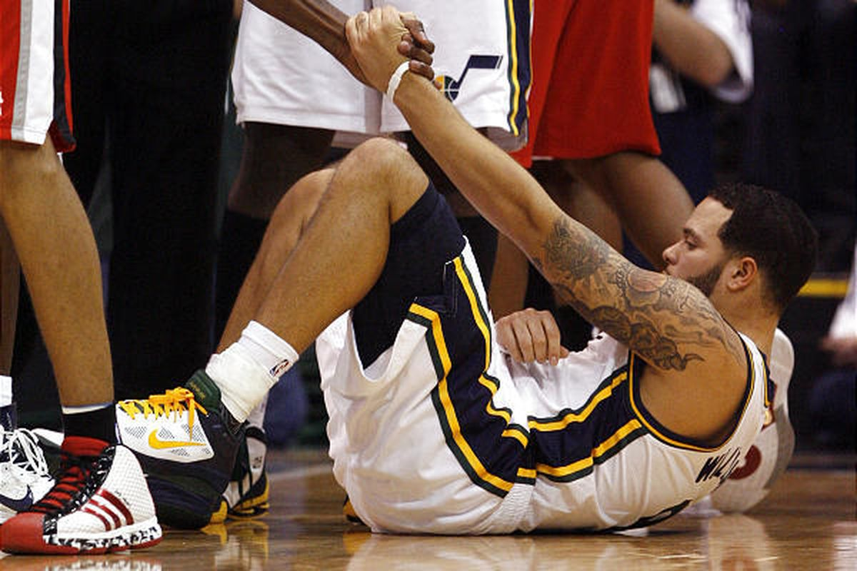 Utah Jazz point guard Deron Williams nurses his right wrist as he is helped up after being fouled.