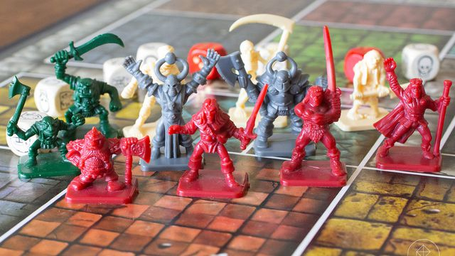 A collection of red, green and grey gaming figures on a boardgame