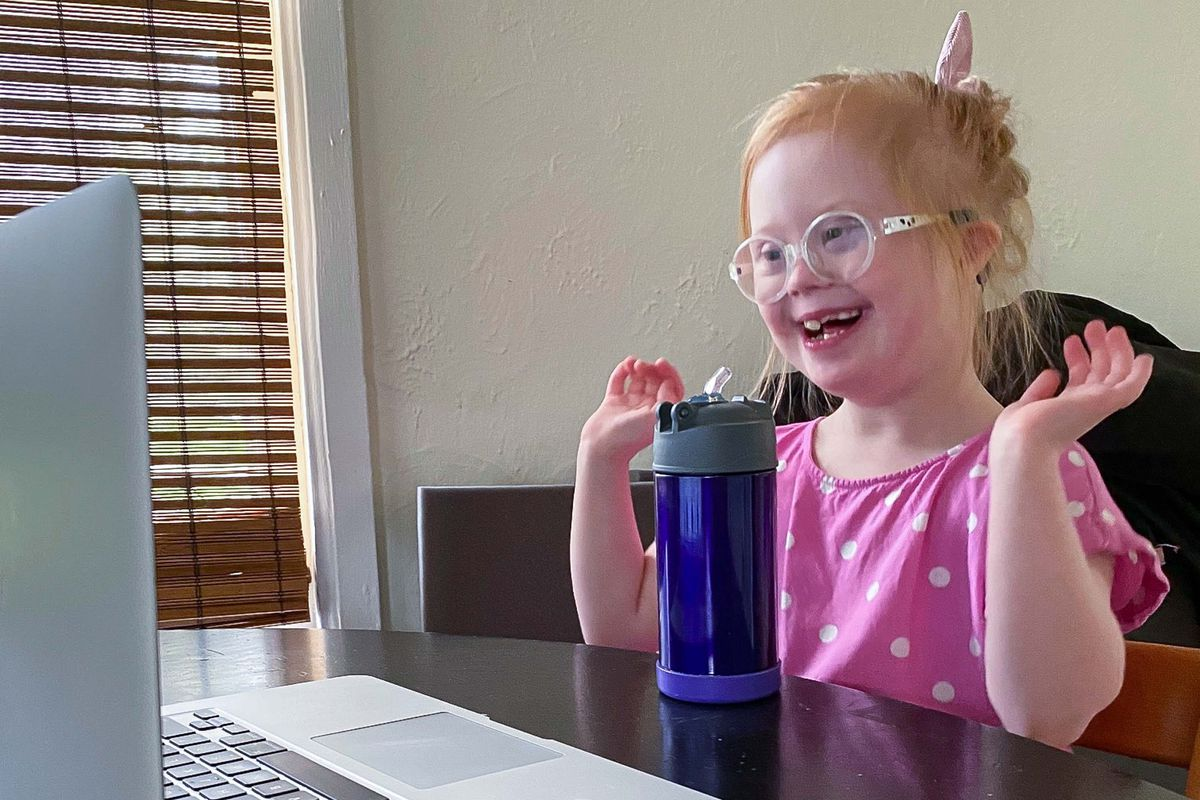 A little girl with Down syndrome smiles while looking at a computer screen. She has red hair and is wearing a pink polka dotted shirt.