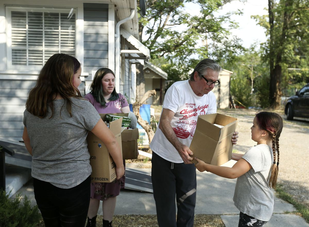 Jerry Dolejs, center, gives food to his neighbors after visiting the Utah Food Bank mobile pantry at The Church of Jesus Christ of Latter-day Saints' Cannon Stake Center in Salt Lake City on Wednesday, Sept. 1, 2021. Dolejs keeps a few items for himself and gives the majority of the food to his neighbor, who has a large family.
