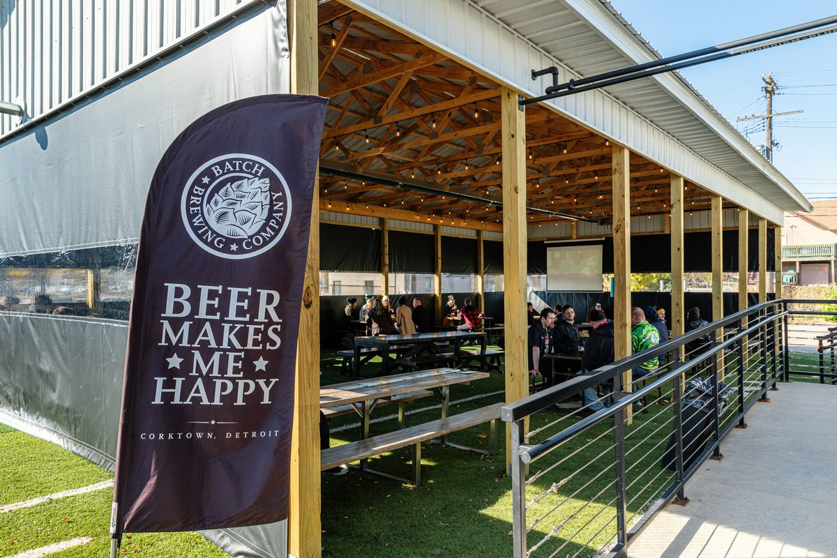 A pole barn outside of Batch Brewing Company features a flag with the brewery's logo that says Beer Makes Me Happy.