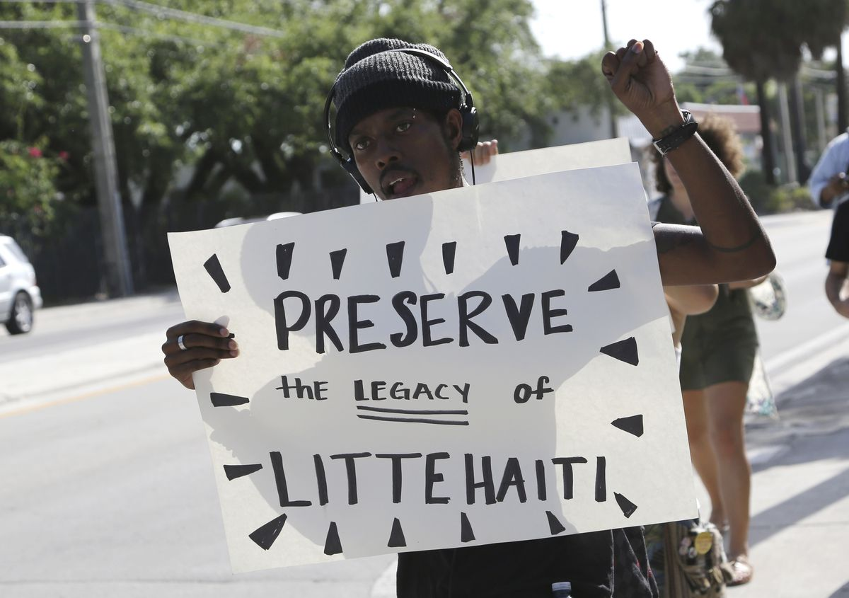 A man wearing a black cap holds up a sign at a protest against a new development in Miami's Little Haiti neighborhood.