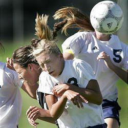 Timpanogos High's Shelby McKell, center, reacts after header in front of Lone Peak's Mikala Wilkes, left.