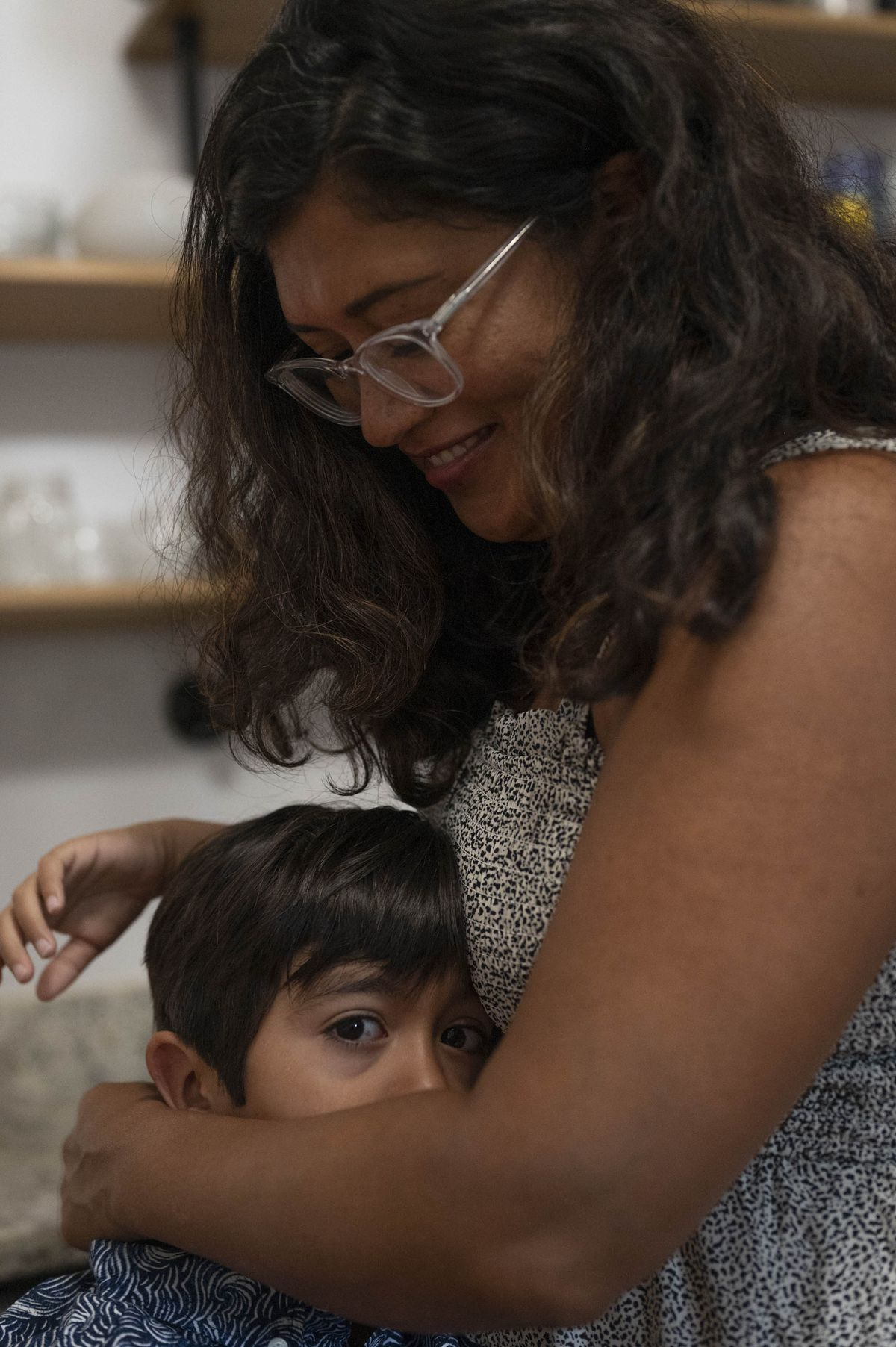 A mother wearing glasses embraces her kindergarten-aged son as he looks at the viewer.