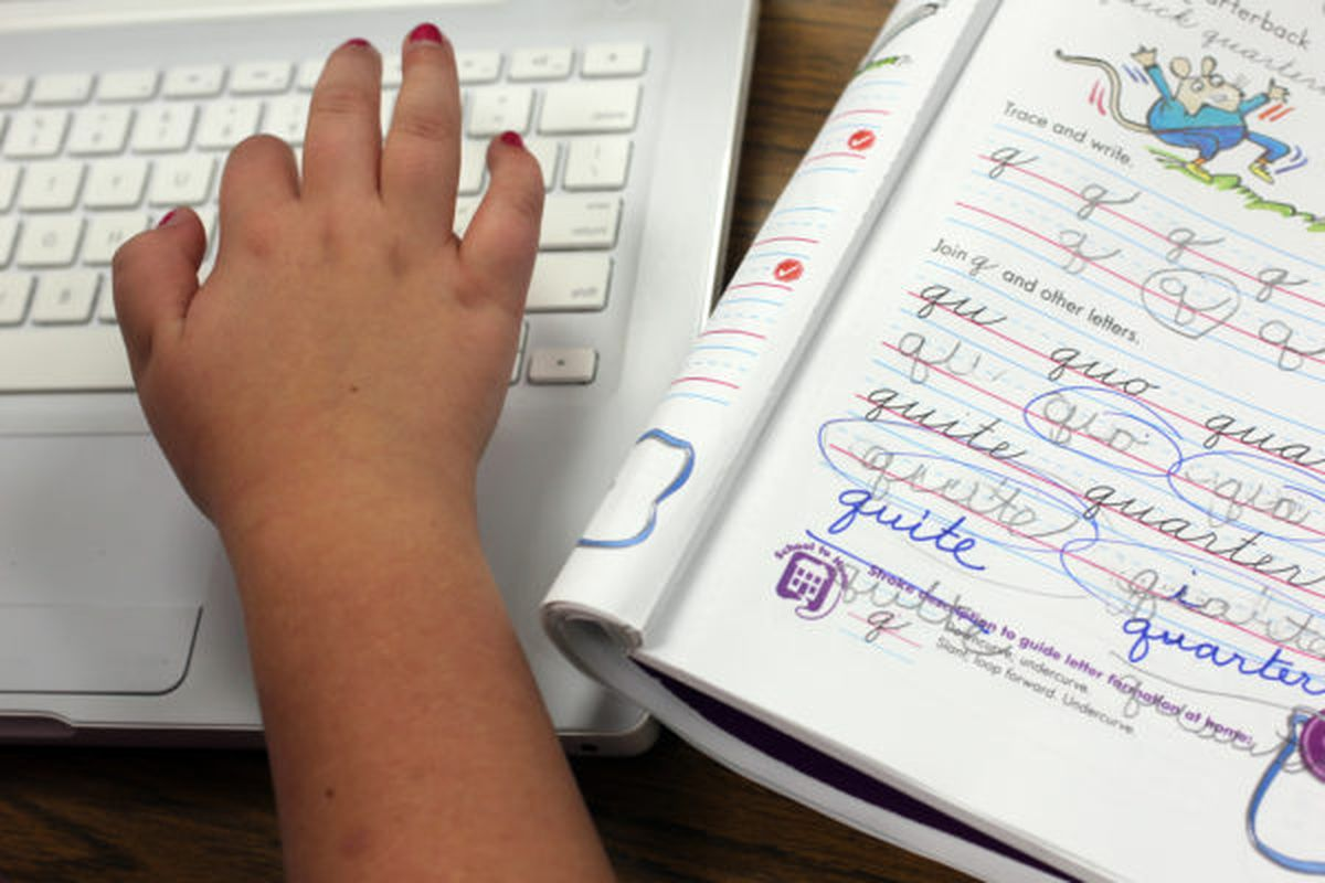 A student types on a laptop after finishing a cursive lesson.