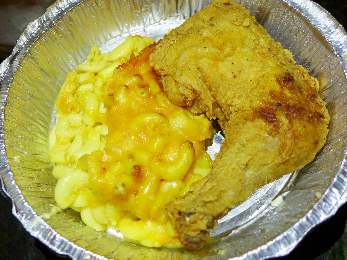 A leg of fried chicken next to a helping of mac and cheese in an aluminum take-out container