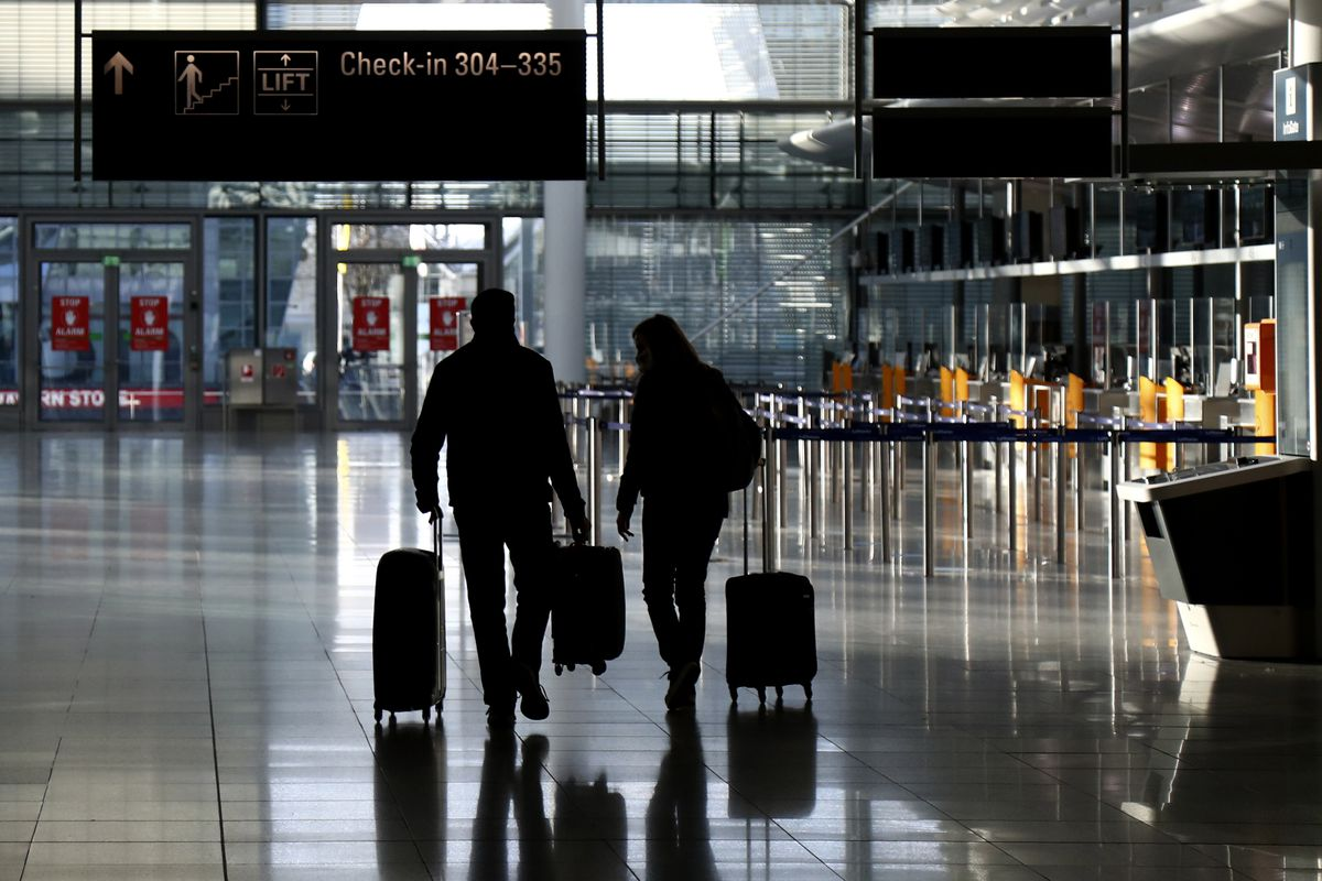 In this Saturday, Dec. 26, 2020 file photo, people walk with their luggage through a deserted check-in hall at the airport in Munich, Germany as Germany continues its second lockdown to avoid the further outspread of the coronavirus.