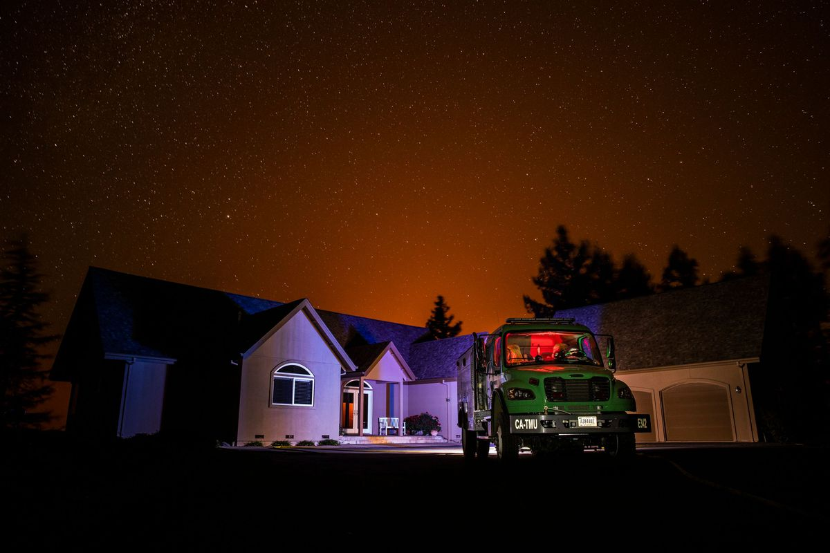 home with a fire engine in front of it. The faint outline of a fire glows in the background.